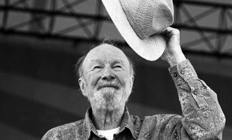 Pete Seeger on stage raising his hat