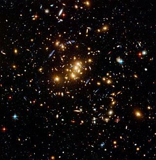 3. El campo gravitacional de este conglomerado de galaxias distorsiona los haces de luz emitidos por galaxias más distantes. Los brillos azules son reflejos de estos haces. Fotografía: Telescopio Espacial Hubble