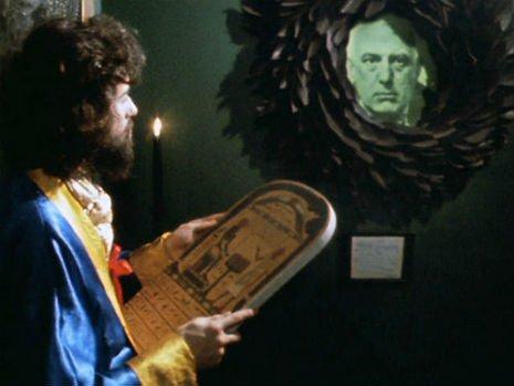 Page en un cameo en Lucifer Rising, frente a un retrato de Crowley